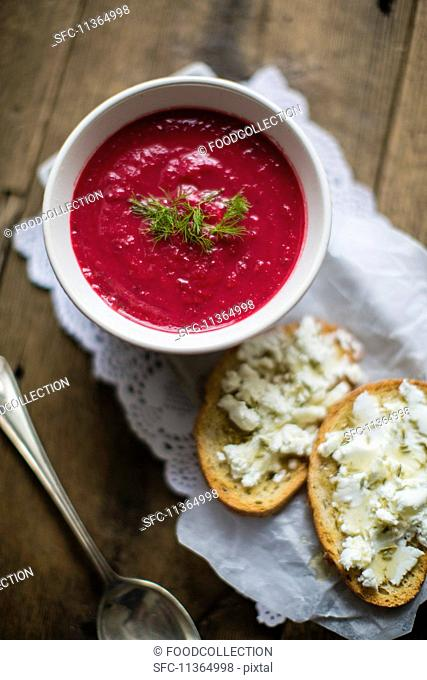 Beetroot soup served with slices of bread spread with cheese