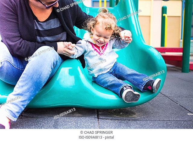 Mother and daughter going down slide in playground