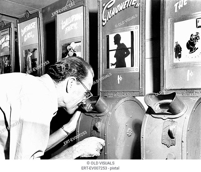 Man looking into a nickelodeon film machine All persons depicted are not longer living and no estate exists Supplier warranties that there will be no model...