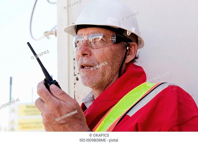 Engineer using walkie talkie on oil rig