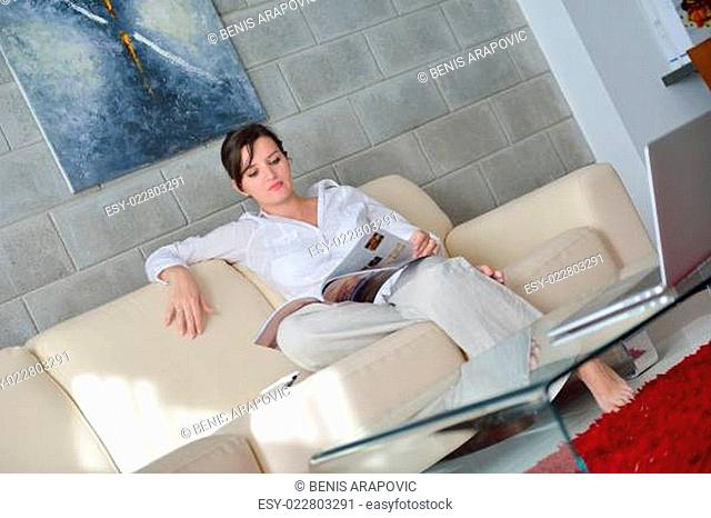 woman reading magazine at home
