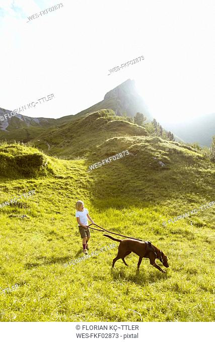 Austria, South Tyrol, young girl hiking with dog