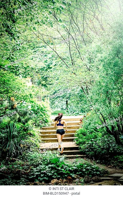 Caucasian woman running on staircase in park