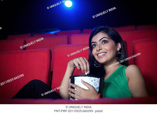 Woman enjoying movie with popcorns in a cinema hall