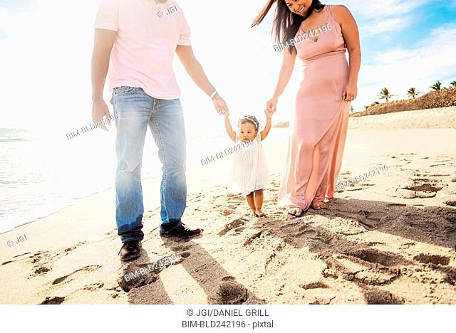Couple holding hands of baby daughter walking on beach