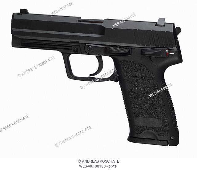 Automatic pistol against white background, close up