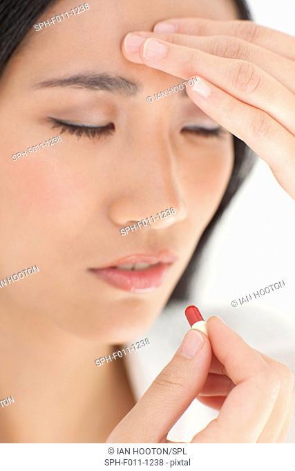 Mid adult woman taking painkiller, portrait