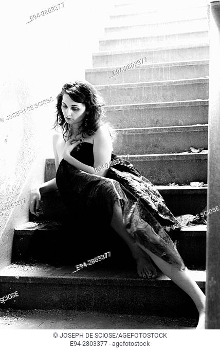 A partially nude 25 year old woman wrapped in fabric sitting alone on a stairway in an old building, black and white