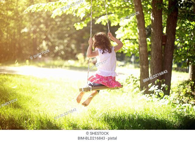 Girl playing on swing in field
