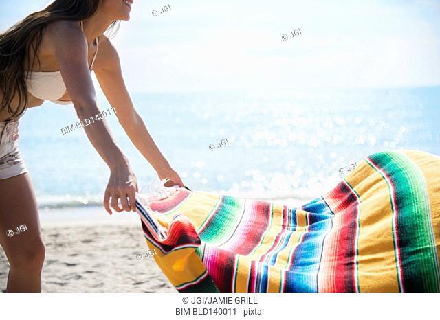 Caucasian woman spreading blanket on beach