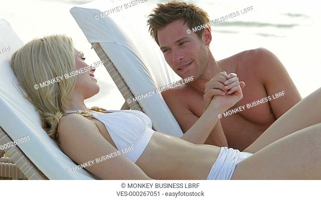 Couple lie on sun loungers holding hands and talking.Shot on Canon 5d Mk2 with a frame rate of 30fps