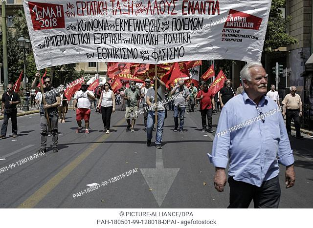 01 May 2018, Greece, Athens: Particpants of a 01 May demonstration carrying flags and banners as they march to the Greek parliament