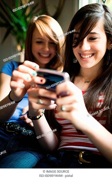 Two teenage girls using smartphone