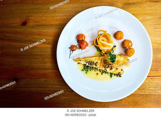 Overhead view of plate with garnished fish and vine tomatoes, Antigua, Guatemala