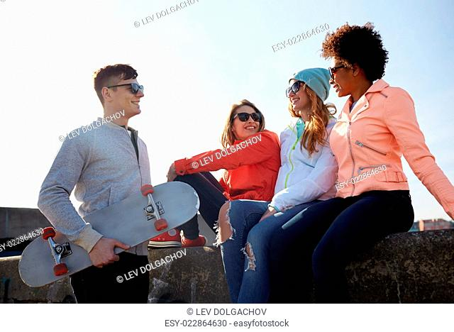 people, leisure and sport concept - group of happy teenage friends with skateboard talking on city street