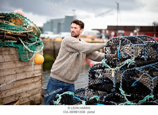 Young fisherman stacking lobster pots in harbour, Fraserburgh, Scotland