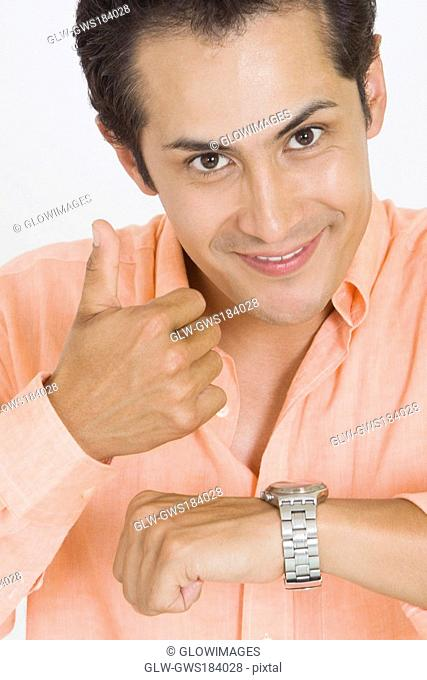 Portrait of a young man giving thumbs up after checking the time on his wristwatch