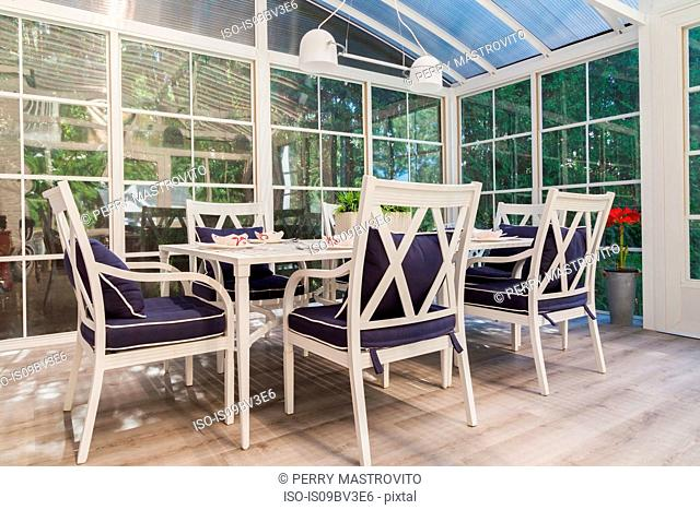 White dining table and armchairs with blue cushions in sunroom
