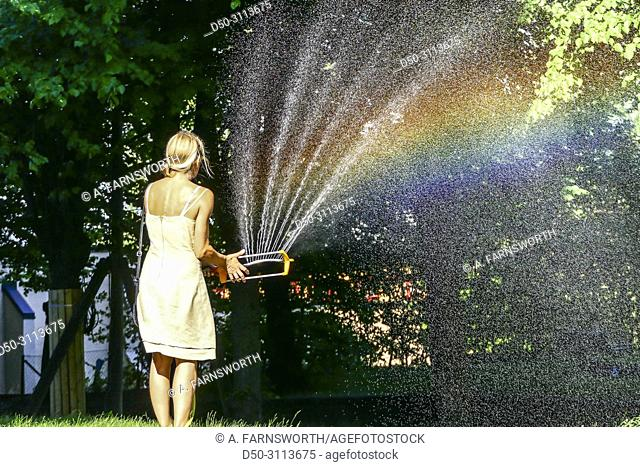 A woman waters the grass with a hose in the Hagalund Park and apartment complex, Solna suburb. Stockholm, Sweden