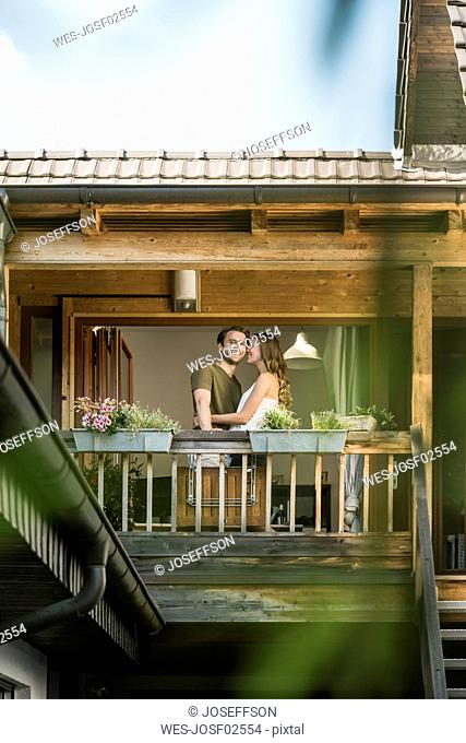 Happy affectionate couple on balcony at home