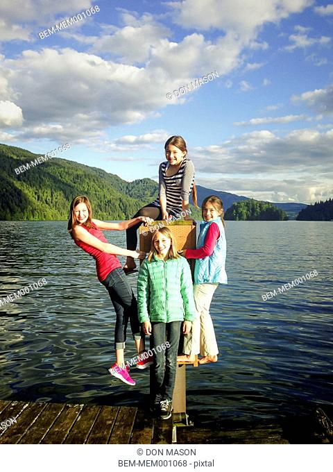Girls playing together on wooden dock