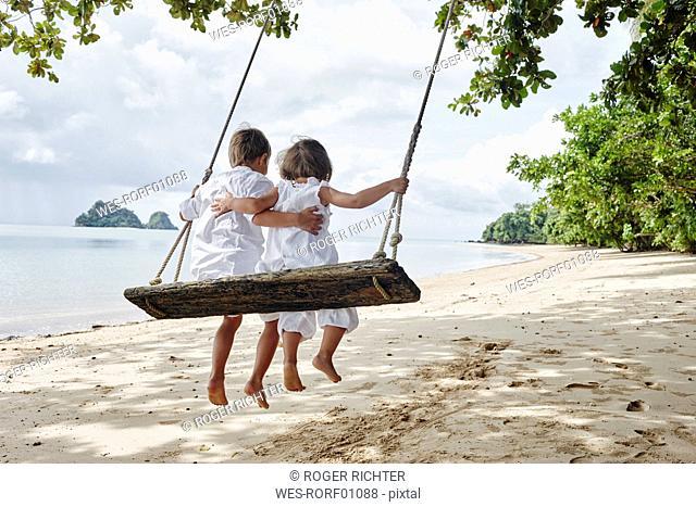 Thailand, Ko Yao Noi, boy and little girl on a swing on the beach