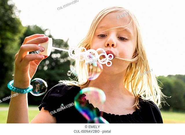 Portrait of cute girl blowing bubbles in park