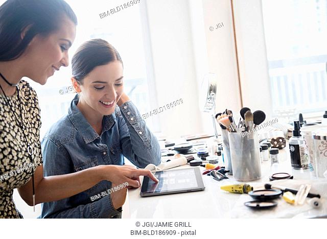 Makeup artist using digital tablet with client