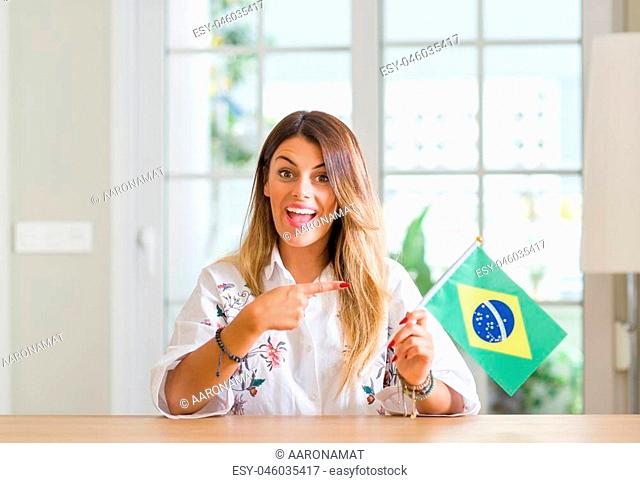 Young woman at home holding flag of Brazil very happy pointing with hand and finger