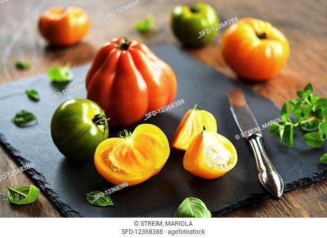 Colorful rustic tomatoes on cutting board with old knife and herbs