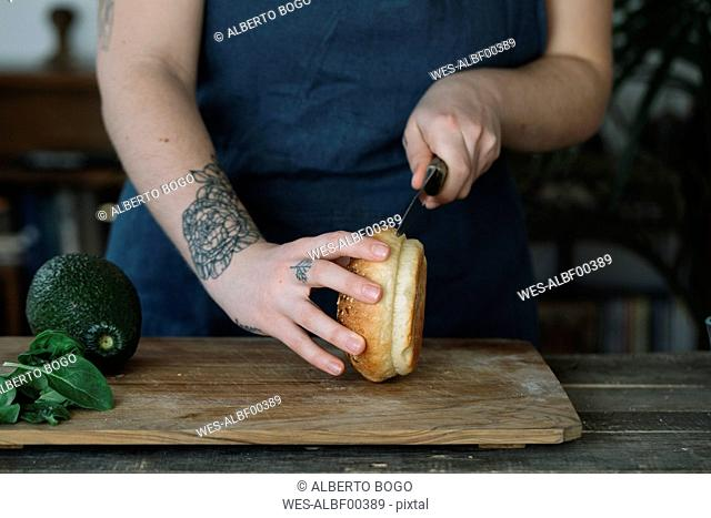 Woman preparing vegan burger, cutting bread roll