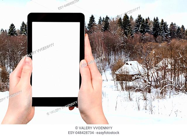 travel concept - tourist photographs of russian village near forest in cloudy winter day in Smolensk region of Russia on smartphone with cut out screen with...