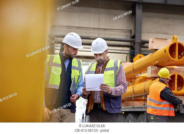 Male foreman and worker reviewing paperwork in factory