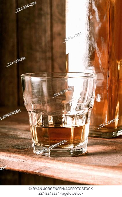 Rustic beverage still life photo on a glass of southern scotch whiskey on wooden table top. Aged alcohol