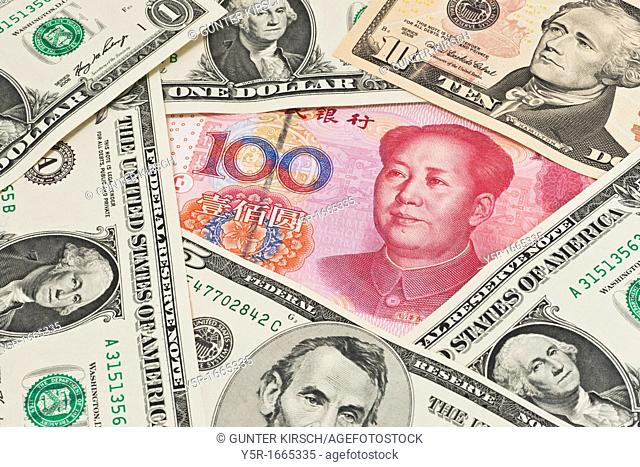 Many U S Dollar bills lying side by side In the middle lies a Chinese 100 Yuan bill with the portrait of Mao Zedong The renminbi, the Chinese currency