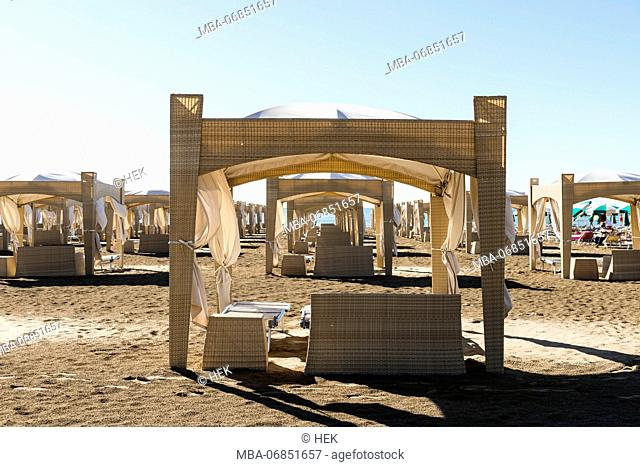 Comfortable wicker furniture with shading on the beach of Lignano