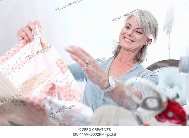 Older woman gathering fabric for sewing