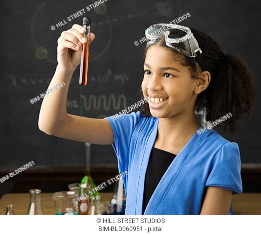 Mixed Race girl looking at vial of liquid