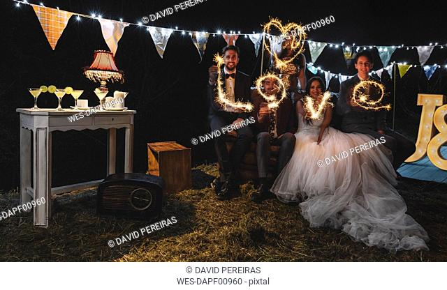 Wedding couple and friends making the word 'love' with sparklers on a night party outdoors
