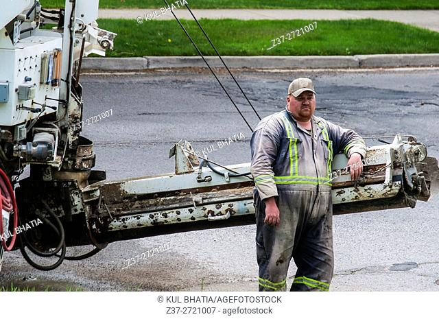 Operator of a concrete mixing truck (ready-mix) waits for other workers, Ontario, Canada