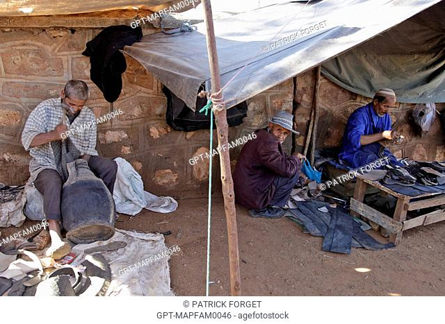 A SHOEMAKER WORKING WITH LEATHER IN THE BAZAAR, BERBER MARKET OF TAHANAOUTE, AL HAOUZ, MOROC