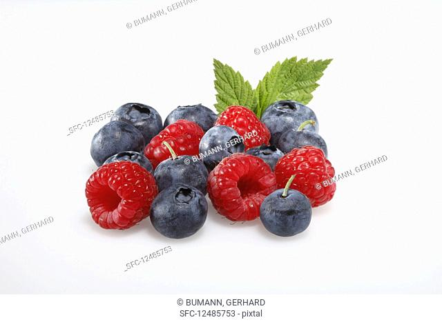 Fresh raspberries and blueberries with a leaf