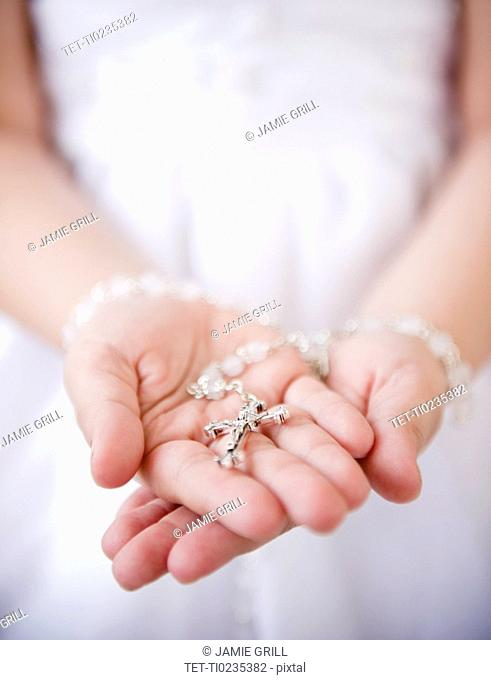 Close up of girl's 8-9 hands holding rosary beads