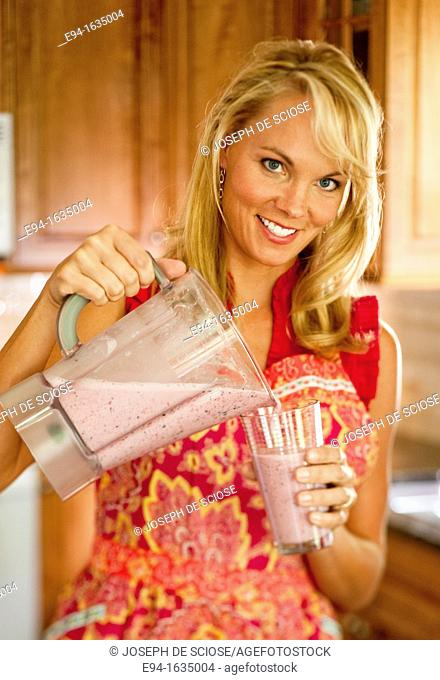 35 year old blond woman standing in a kitchen pouring a cold fruit drink from a blender into a glass