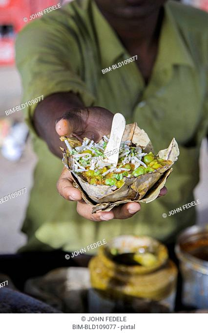Hand holding bowl of food