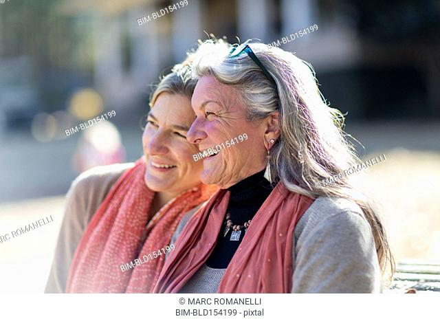 Caucasian mother and daughter sitting outdoors