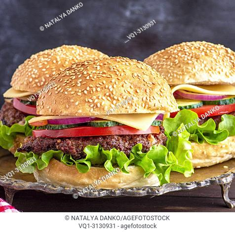 burger with fried cutlet, cheese and vegetables in a round wheat flour bun, close up