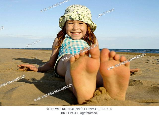 Girl lying and playing on the beach, seaside of the Adria, Bibione, Venetia, Venice, Italy, Europe