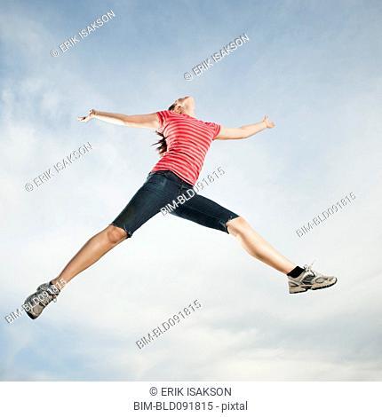 Caucasian teenager jumping in air