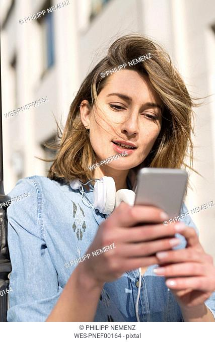 Portrait of woman with headphones looking at cell phone